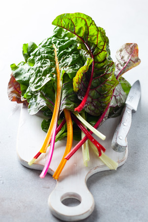 Various different coloured chard leaves on a gray surface Stock Photo