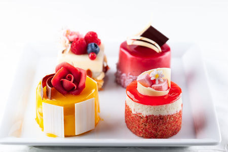 Various mini cakes on a white plate. Sweets decorated with fresh berries and flowers for holiday. Stock Photo