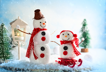 A festive winter background with two happy snowmen made from balls of yarn, buttons and lace. Christmas card, copy space.