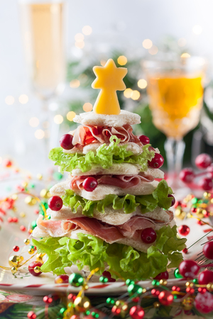 Christmas tree from toasted bread, lettuce, ham and cheese. Festive idea for Christmas or New Year dinner.