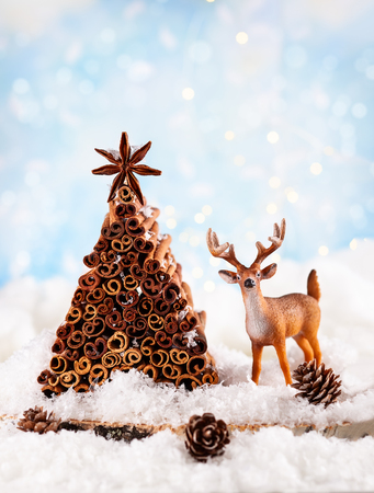 Christmas holiday concept with deer, pine cone and Christmas tree made from stock of cinnamon and anise star.