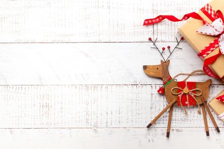 Decorazioni natalizie e contenitori di regalo su fondo di legno bianco.