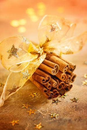 Christmas concept with bunch of cinnamon sticks tied with golden ribbon
