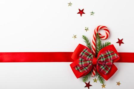 Nastro rosso di Natale con fiocco e cono di caramelle su sfondo bianco. Vista dall'alto. Decorazioni natalizie per confezione regalo.