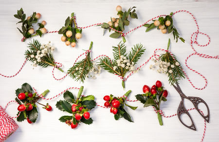 Making natural Christmas  garlands  with fresh flowers,leaves,berries and fir branches.