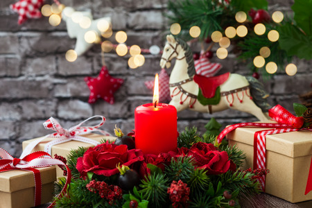Christmas decorations with red candle,gift boxes and rocking horse on  the old wooden table Stok Fotoğraf