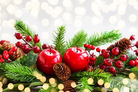 Decoración navideña con abeto, piñas, manzanas rojas y bayas de acebo