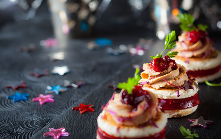 Festive appetizer with foie gras, cranberry chutney and jelly. Selective focus