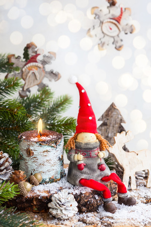 Christmas decoration with toy santa, burning candle,fir branches and pine cones