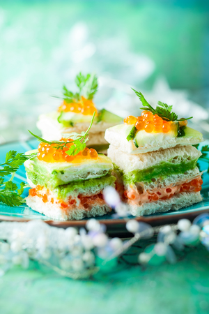 Striped sandwiches with red caviar,cucumber and avocado for holiday Stock Photo