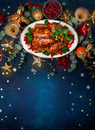 Concept of Christmas or New Year dinner with roasted chicken and various vegetables dishes. Top view. Banco de Imagens