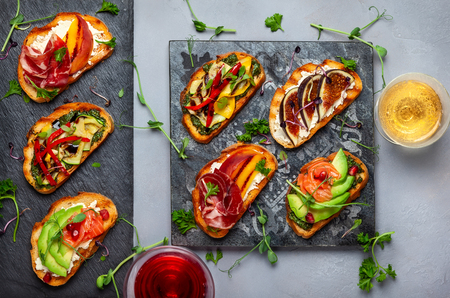 Set of assorted bruschetta  with various toppings for holiday on the stone board. Top view. Party food concept. Banque d'images - 111584355