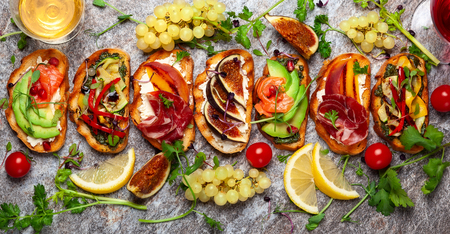 Set of assorted bruschetta  with various toppings for holiday on the stone board. Top view. Party food concept. Banque d'images - 111584357