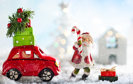 Santa Claus and red toy car carrying Christmas gifts in snowy landscape. Christmas concept with copy space. Stock Photo