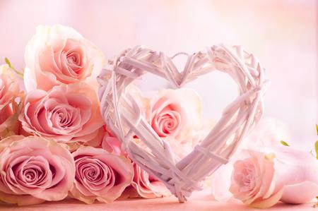 Festiva natura morta con rose rosa e cuore in legno.