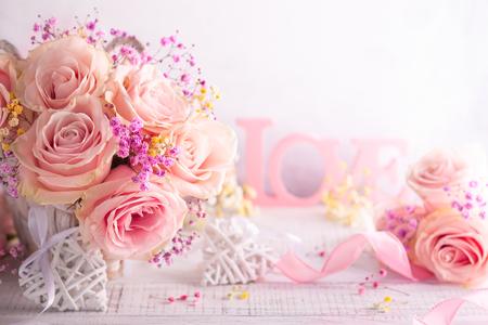 Piękne różowe róże w koszu na vintage drewnianym stole. Styl w stylu shabby chic. Kompozycja kwiatowa na wakacje z miejsca na kopię.