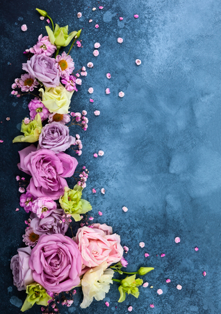 Beautiful  flowers on vintage blue background. Festive floral concept with clean space for text. Top view.