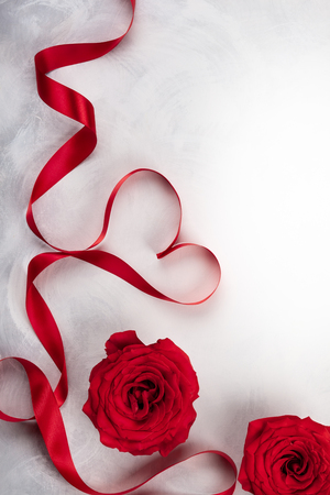 Red roses and red ribbon in shape of heart on the vintage white-grey background. Festive concept for Valentines day. Top view with copy space.