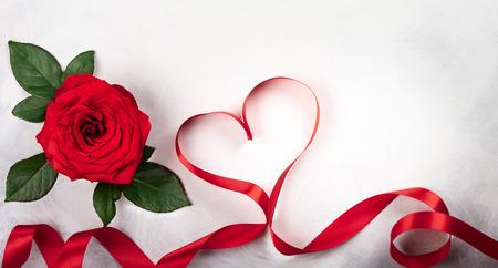 Rotrose auf dem weiß-grauen Hintergrund der Weinlese. Festliches Konzept zum Valentinstag. Draufsicht mit Kopienraum.