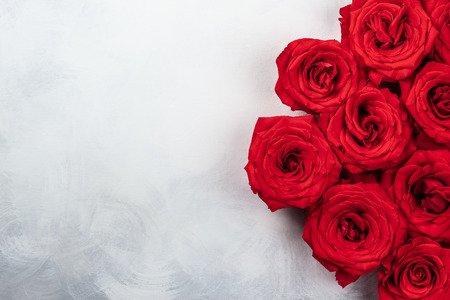 red roses on the vintage white-grey background. Festive concept for Valentines day. Top view with copy space. Stock Photo