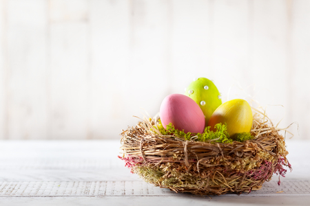 Easter composition with colorful Easter eggs in nest on wooden