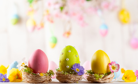 Easter composition with colorful Easter eggs and spring flowers on wooden background. Easter card with copy space. Stock Photo