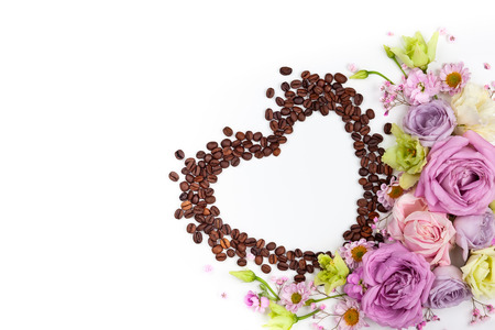 Festive concept for Valentine day or Mother's day with flowers and coffee beans in shape of heart on white background. Valentine day greeting card, top view, flat lay. Stock Photo