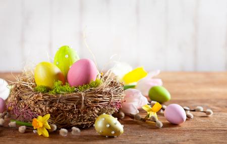 Osterkomposition mit bunten Ostereiern im Nest, Frühlingsblumen und Zweigen von Weidenkätzchen auf Holzhintergrund. Osterkarte mit Kopienraum.