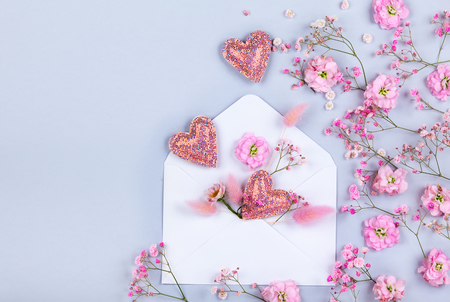 Spring floral composition made of fresh pink flowers,envelope and hearts on light pastel background. Festive flower concept. Flat lay, top view with copy space. Stock Photo