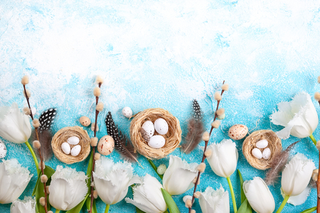Easter composition with Easter eggs in nest,pussy willow branches and white tulips on the blue background. Bunch of spring flowers and Easter decor. Top view with copy space.