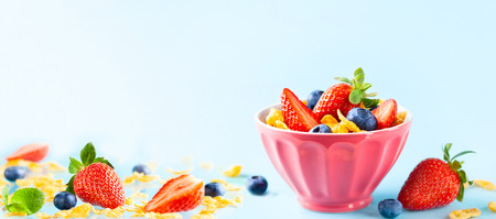 Concept of healthy gluten free breakfast with berries, natural yogurt and corn flakes in the pink bowl on blue