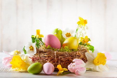 Composizione pasquale con uova di Pasqua colorate nel nido, fiori primaverili Archivio Fotografico