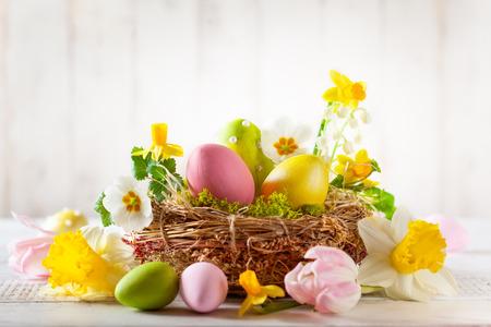Osterkomposition mit bunten Ostereiern im Nest, Frühlingsblumen Standard-Bild