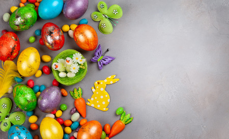 Colorful Easter eggs,chocolate Easter sweets, bunny and nest with chicks  on grey Stock Photo - 119186354