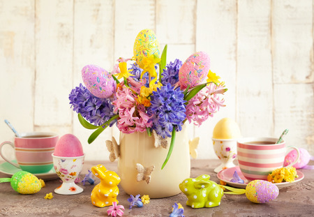 Easter breakfast table with tea, eggs in egg cups, spring flowers in vase and Easter decor. Stock Photo