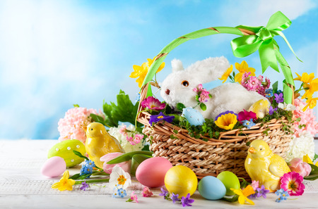 Easter composition with little white bunny in basket, chicks, spring flowers and colorful Easter eggs