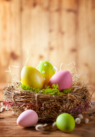 Easter composition with colorful Easter eggs in nest and branches of pussy willows on wooden