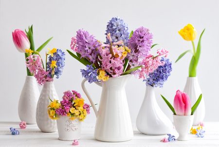 Beautiful spring flowers bouquets in various vases on the white background. Flowers festive composition. 免版税图像