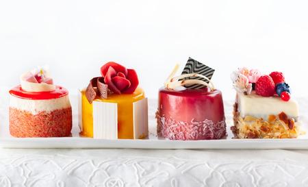 Varios mini pasteles en un plato blanco. Dulces decorados con flores y bayas frescas para vacaciones. Foto de archivo