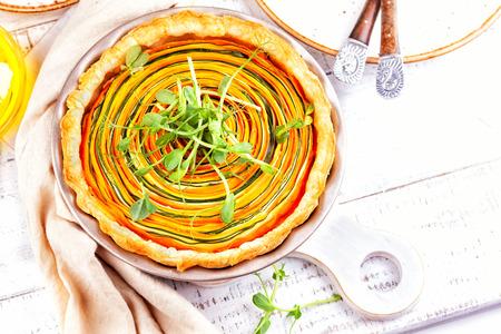 Domowa tarta warzywna z marchewką, cukinią i dynią na białym drewnianym stole. Spiralna tarta warzywna.