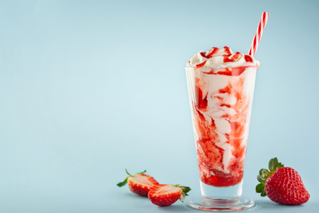 Strawberry milkshake with whipped cream and berry syrup in the tall glass on blue background.