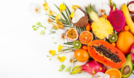 Still life with fresh assorted exotic fruits on a palm leaf. Concept of healthy eating with fruits and tropical flowers. Top view.