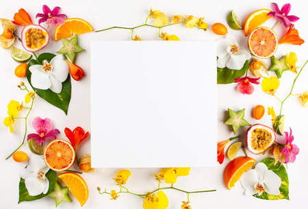 Blank card and exotic fruits with tropical leaves and flowers on white background