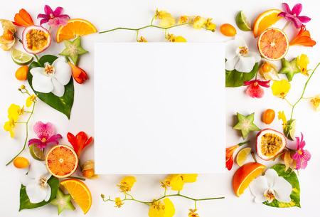 Lege kaart en exotische vruchten met tropische bladeren en bloemen op witte achtergrond