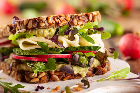 Fresh vegetarian  sandwich  with creamy avocado, cheese and fresh veggies the wooden board. Imagens