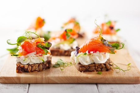 Mini canapes with smoked salmon, soft cheese and fresh veggies on gluten-free seed bread for party. Imagens - 122840203