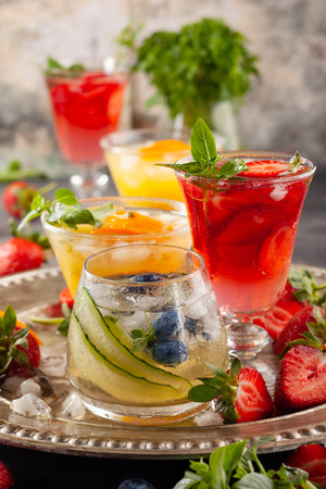 Assortment summer non-alcoholic cocktails with fresh berries, herbs and fruits on dark