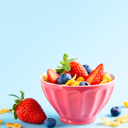 Concept of healthy gluten free breakfast with berries,natural yogurt and corn flakes in the pink bowl on blue