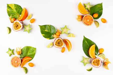 Colorful pattern of whole and sliced exotic fruits with tropical leaves and flowers.