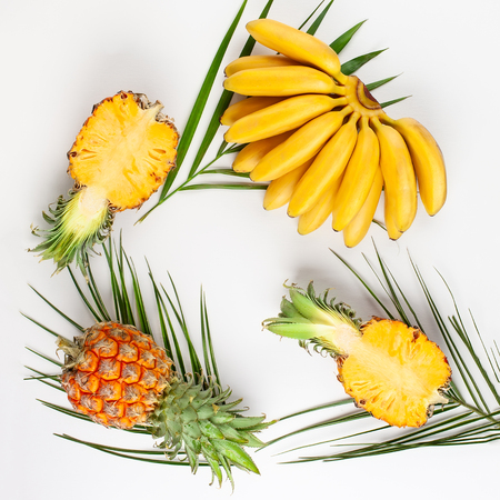 Summer composition with exotic fruits and tropical leaves on white